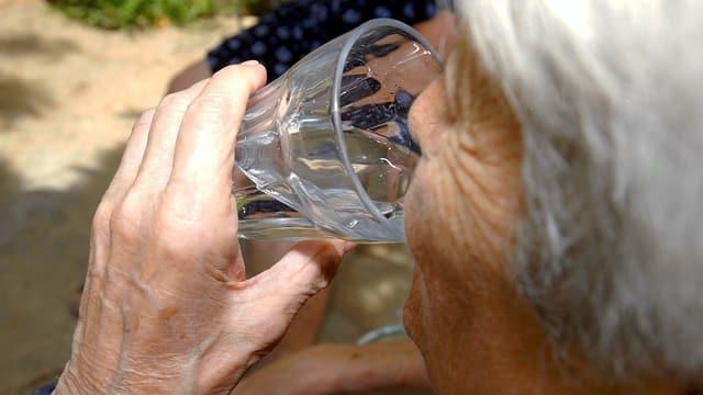 Eine ältere Frau trinkt ein Glas Wasser