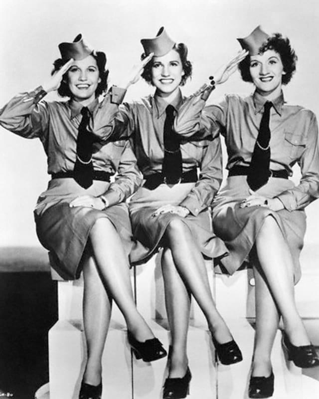 Die Andrews Sisters in Militär-Outfit zeigen Bein und salutieren.