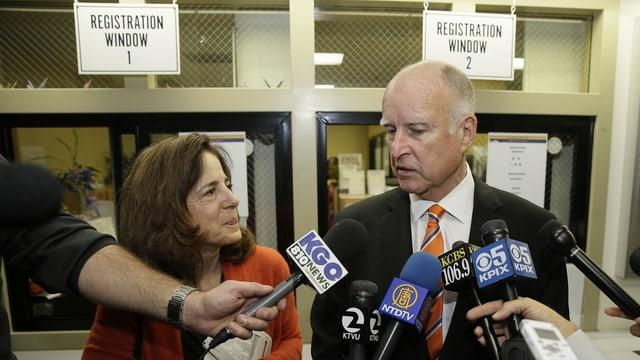 Eine Frau und ein Mann stehen vor Mokrofonen.