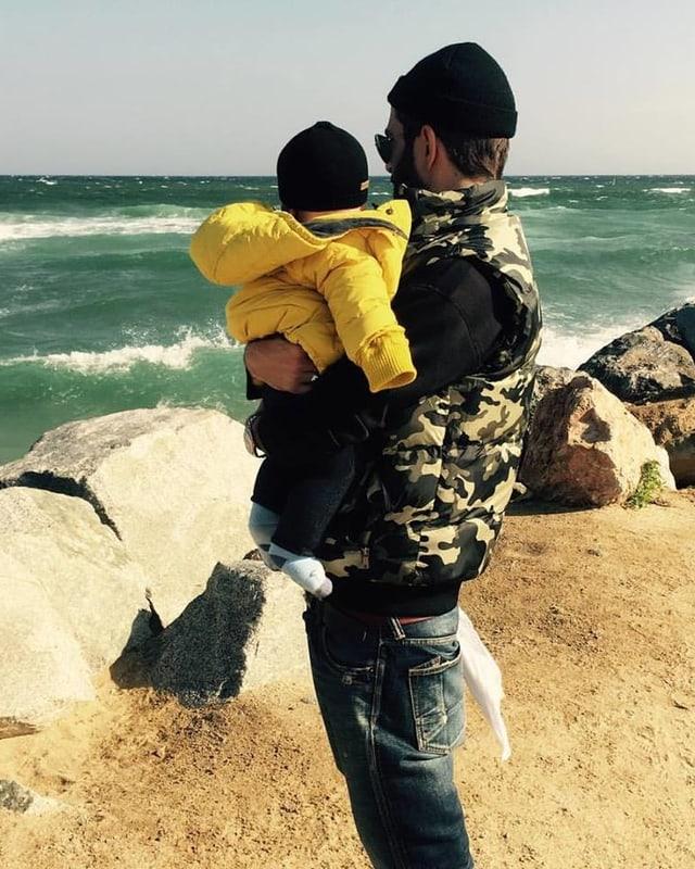 Bligg steht mit seinem Sohn im Arm vor dem Meer. Beide mit dem Rücken zu uns gewandt.