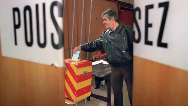 Stimmbürger hinter einer Klapptüre steckt einen Stimmzettel in eine Urne