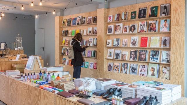 Bücherregal in einem Laden, im Vordergrund ein Podest, auf dem neben Zeitschriften auch Schuhe und Taschen zu sehen sind.