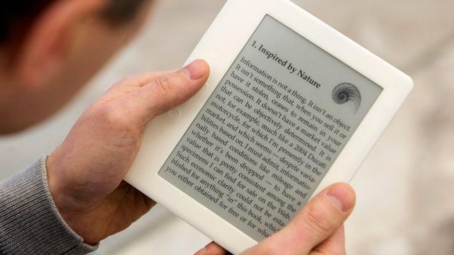Ein Mann liest ein Buch mit einem eReader.