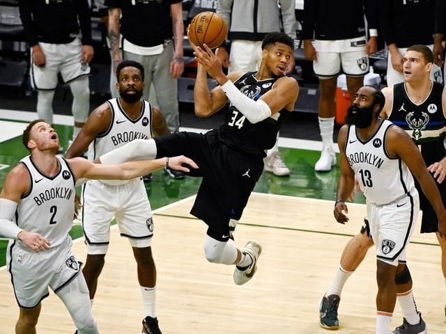 Bucks-Superstar Giannis Antetokounmpo umringt von Nets-Spielern.