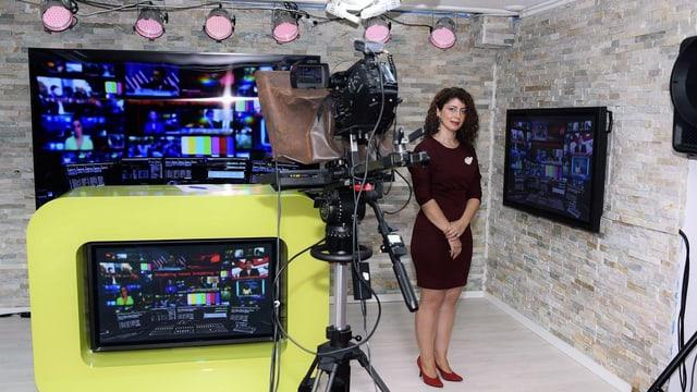 Eine Frau steht in einem Fernsehstudio. Im Vordergrund ist eine Kamera zu sehen.