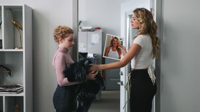 Eine kleinere Frau wird von einer grösseren als Kleiderständer missbraucht.