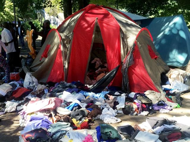 Viele Kleider liegen vor einem Zelt.