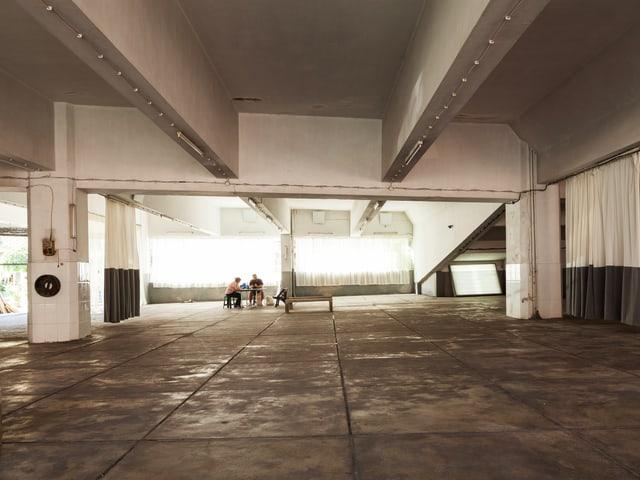 Am Ende eines industriell anmutenden Raumes sitzen zwei Menschen an einem Tisch.