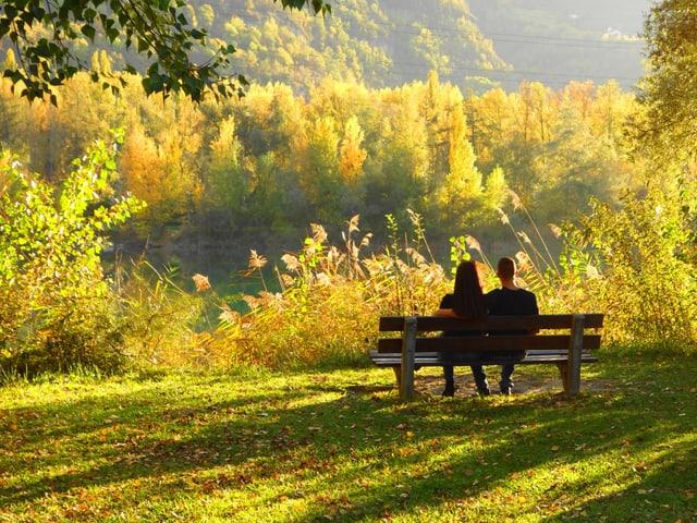 Letzter warmer Herbsttag, Wanderere ruhen sich auf einer Bank aus.