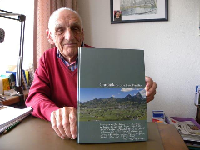 Der Senior zeigt mit stolzem Blick die Familienchronik in Buchform.