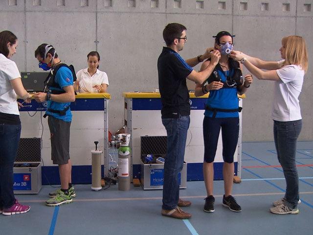 Verschiedene Personen legen Testpersonen ein Gerät an.