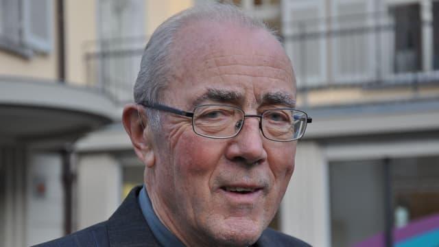 Der 80-jährige Martin Bundi Lächelt verschmitzt in die Kamera. Er trägt eine Brille.