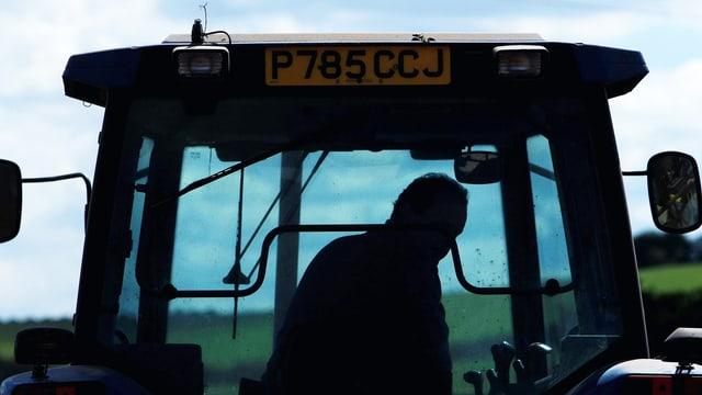 Silhouette eines Bauern, der Traktor fährt.
