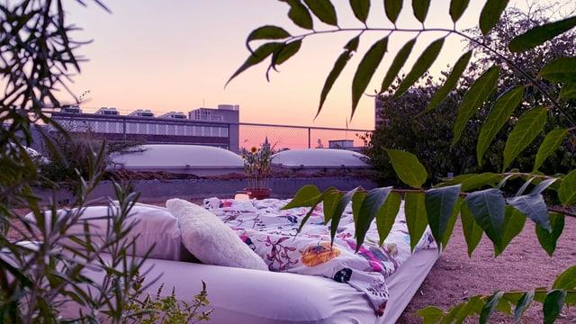 ein Bett im Garten, im Hintergrund sieht man den Sonnenuntergang