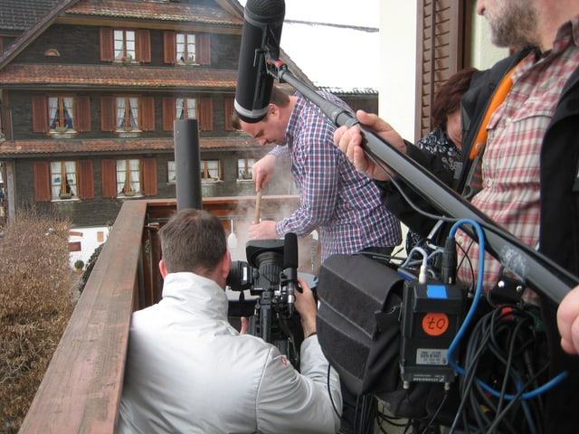 Filmteam über dampfendem Kessel.