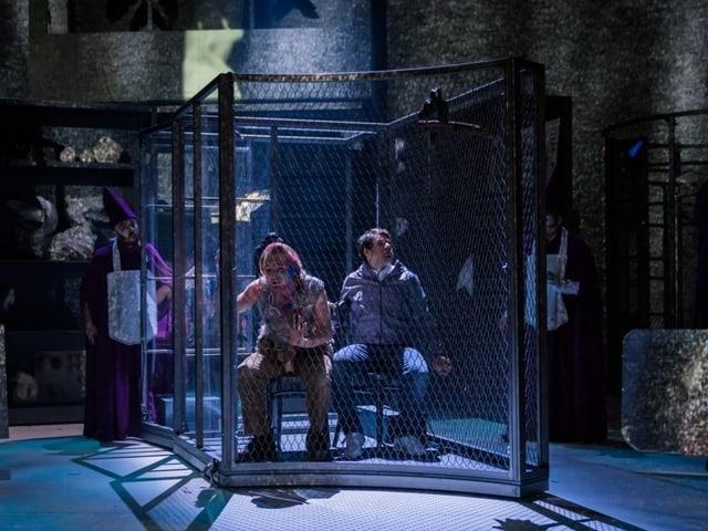 Zwei Männer sitzen in einem grossen Käfig auf einer Bühne.