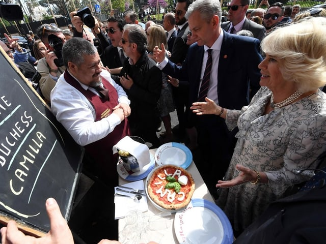 Camilla steht vor einem Tisch, auf dem eine Pizza liegt. Aus Mozzarella ist darauf ihr name geformt.