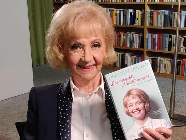 Eine ältere blondhaarige Frau mit einem Buch in der Hand.