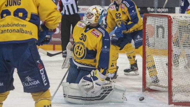 In goli da hockey sin schanuglias davant il gol e dus ulteriurs giugaders da hockey che stattan dretg si.