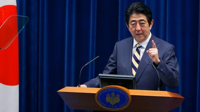 Japans Ministerpräsident Shinzo Abe neben einer japanischen Flagge an einem Rednerpult.