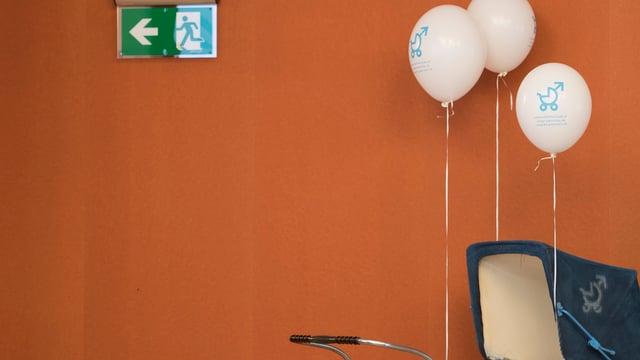 Ein Kinderwagen mit Ballons steht vor einem Exit-Schild.