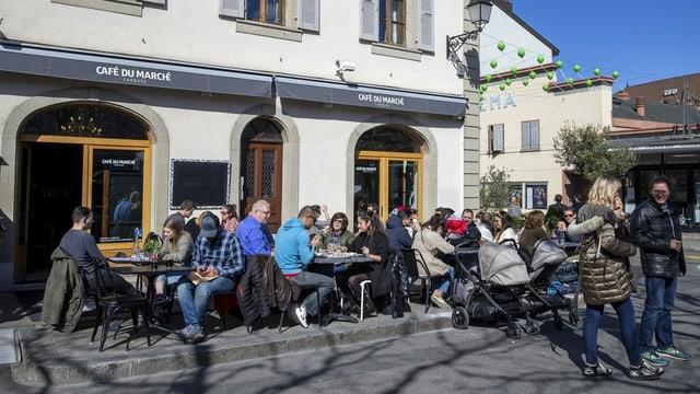 Gäste sitzen auf einer Terrasse eines Cafes.
