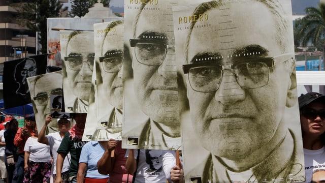 Ein Menschenumzug auf einer Strasse hält grosse Porträt-Bilder von Romero in die Höhe.
