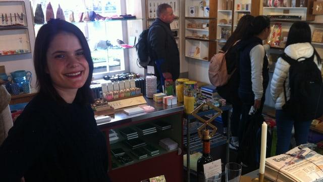 Eine junge Frau steht in einem Laden und lächelt, dahinter stehen Kunden