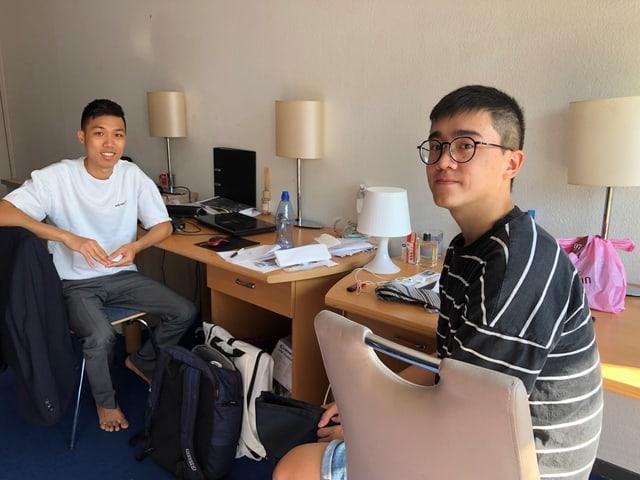 Zwei junge Asiaten sitzen nebeneinander an Schreibpulten.