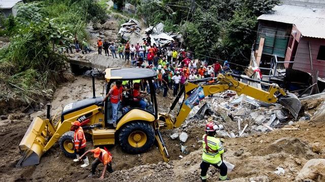 Bulldozer an einem Hügel mit zerstörten Gebäuden