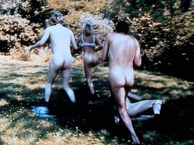 Drei nackte Personen rennen über eine Wiese.