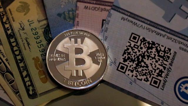 Eine Bitcoin-Münze, daneben Dollarscheine und ein Zertifikat für Bitcoins.