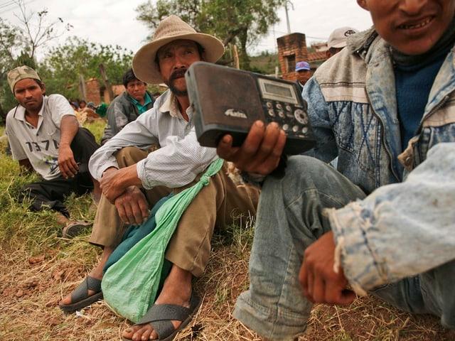 Südamerikanische Landarbeiter hören Radio.