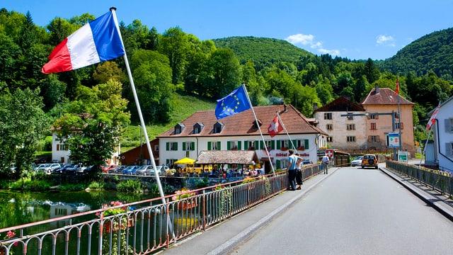 Frankreich-, EU- und Schweizerflagge, Gebäude, Wald im Hintergrund