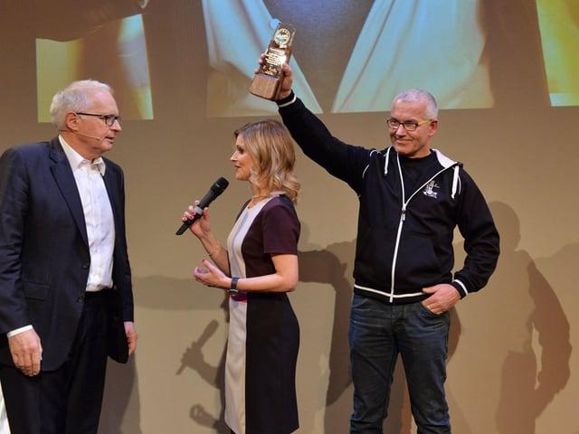 Thomas Niederer streckt auf der Bühne den Pokal in die Luft.