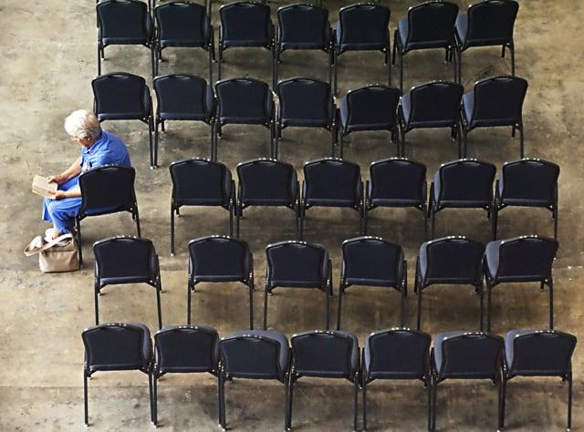 Eine Frau sitzt alleine auf einem von vielen Stühlen und liest.