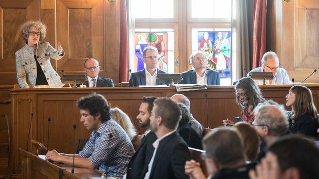 Ratssaal, vorne Köpfe von Parlamentariern, hinten Stadträte, Stadpräsidentin spricht