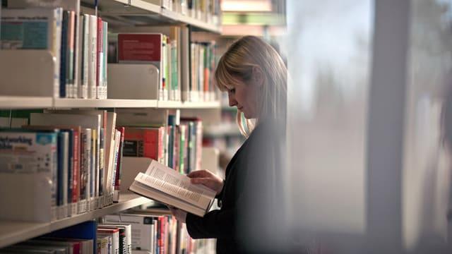 Eine Frau liest ein Buch zwischen Bücherregalen in der Universitätsbibliothek.