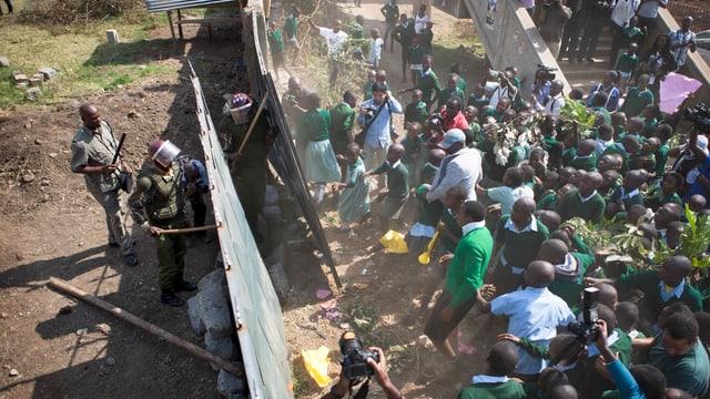 Dutzende Kinder stehen sich Polizisten in Kampfuniform gegenüber, dazwischen das Tor, das zum fraglichen Grundstück führt.