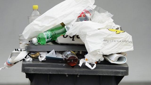 Eine schwarze überfülte Abfalltonne. Plastiksäcke und PET-Flaschen fallen heraus.
