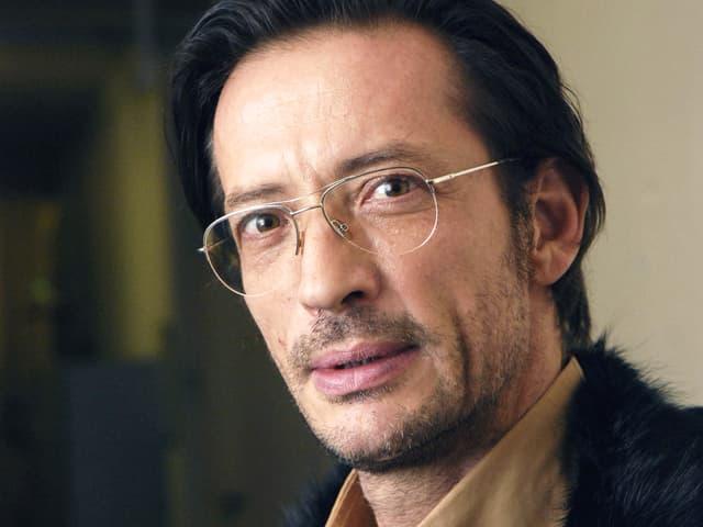 Porträt eines Mannes mit dunklen Haaren und Brille