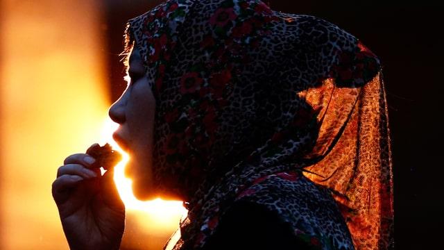 Eine Frau mit Kopftuch führt ein kleines Stück Brot zum Mund.