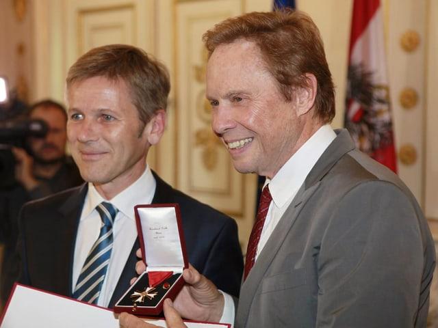 Peter Kraus hält Ehrenmedallie in Händen und lächelt.
