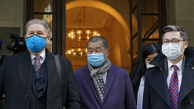 Drei Männer mit Masken kommen aus einem Gebäude.