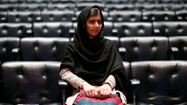 Yousafzai alleine in einem bestuhlten Saal