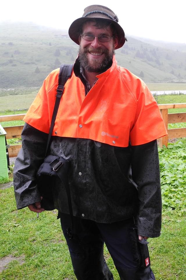 Ludwig Willmann mit orangefarbenem, regendichtem Umhang über wetterfester Kleidung und seiner Tasche mit wichtigen Utensilien über der Schulter.