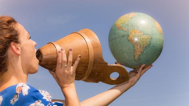 Frau jodelt und hält einen Globus in der Hand