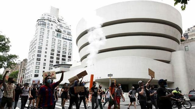 Menschen protestieren auf der Strasse vor einem grossen weissen Gebäude