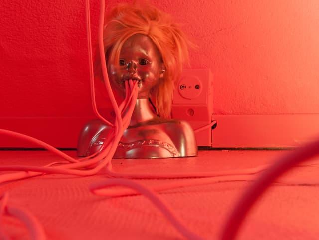 Eine bis zur Brust reichende Puppe, aus deren Mund Kabel laufen.