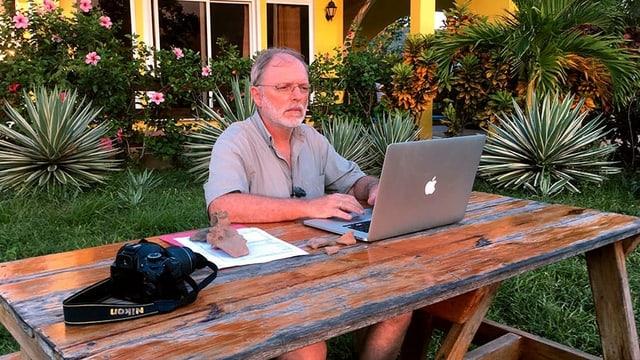 ein Mann sitzt im Garten am Laptop